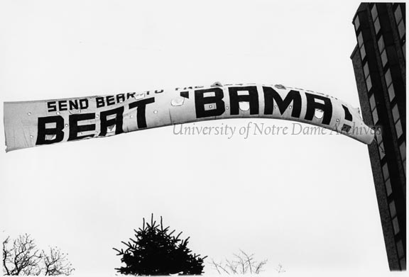 "Football Game Day - Notre Dame vs. Alabama, November 1976.  A banner sign hanging between Grace and Flanner Halls that reads ""Beat 'Bama."""