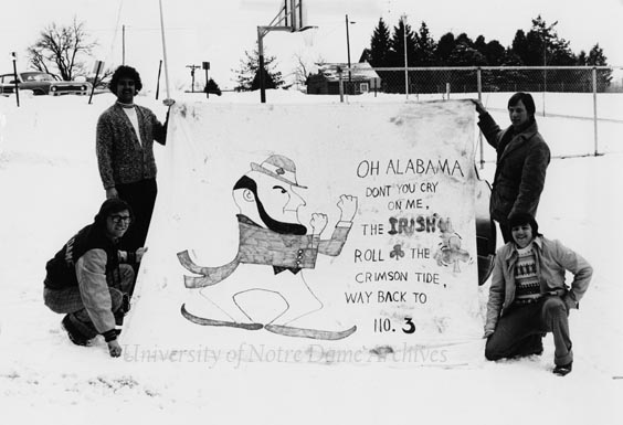 "Four students standing outside in winter with snow with a banner with a drawing of the Leprechaun and text that reads ""Oh Alabama, don't you cry on me, the Irish'll roll the Crimson Tide way back to No. [number] 3"" in regards to the 1973 Sugar Bowl football game, December 1973."