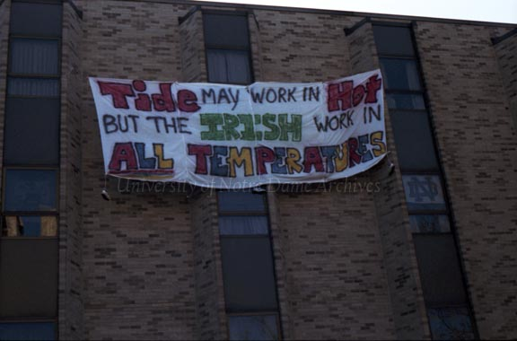 "A banner hanging from Pasquerilla Hall East that reads ""Tide may work in hot but the Irish work in all temperatures,"" regarding the Notre Dame vs. Alabama football game, 1987.Caption:  ""A Sign of Pride.  As Pasquerilla East shows, the Fighting Irish spirit is evidenced all over our campus, not just in the football stadium."""