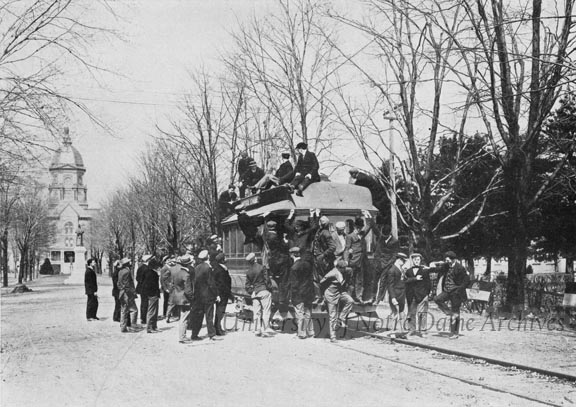 "A group of students climbing onto a streetcar on Main Quad, 1907/0914. Caption:  ""Meeting the First Car, September 14, 1907"""