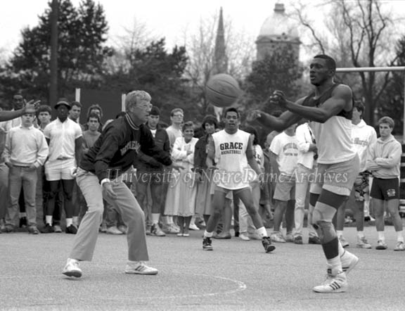 Bookstore Basketball Game with Football Coach Lou Holtz and player Tim Brown on outdoor courts, April 1987