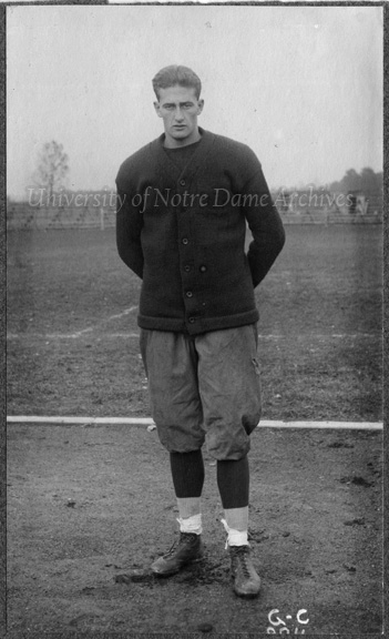 Football Player Rupert Mills, full-length portrait in uniform and monogram sweater, c1913.