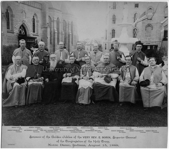 "Souvenir of the Golden Jubilee of the Very Rev. Edward Sorin, August 15, 1888. Seated:  Bishop Richard Gilmour (Cleveland), Archbishop William H. Elder (Cincinnati), Father Sorin, Cardinal James Gibbons (Baltimore), Archbishop John Ireland (St. Paul), Bishop Joseph Dwenger (Fort Wayne), Bishop John Watterson (Columbus), Bishop Richard Phelan (Pittsburgh) Standing:  Bishop James Ryan (Alton), Bishop John Janssen (Belleville), Bishop John Keane (Washington, D.C.), Bishop Maurice F. Burke (Cheyenne), Bishop John Lancaster Spalding (Peoria), Bishop Steven V. Ryan (Buffalo), Bishop Henry J. Richter (Grand Rapids). The group is seated between Sacred Heart Church Basilica and the Main Building. Photo by A. McDonald of McDonald Studio, South Bend, Indiana.  The 09/08/1888 issue of Scholastic, page 48, mentions that copies of this photograph are being sold ""at the low price of $1.00 each."""