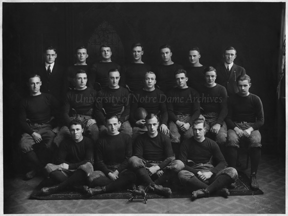 GSBC 1/02: Football Team with a toy mule, 1913. Back Row: Assistant Coach Edwards, Emmett Keefe, Ray Eichenlaub, Albert King, Freeman (Fitz) Fitzgerald, Charles (Sam) Finegan, Coach Jesse Harper Middle Row: Ralph (Zipper) Lathrop, Keith (Deak) Jones, Joe Pliska, Captain Knute Rockne, Gus Dorais, Fred (Gus) Gushurst, Al Feeney Front Row: Allen (Mal) Elward, Alfred (Dutch) Bergman, Bill Cook, Art (Bunny) Larkin