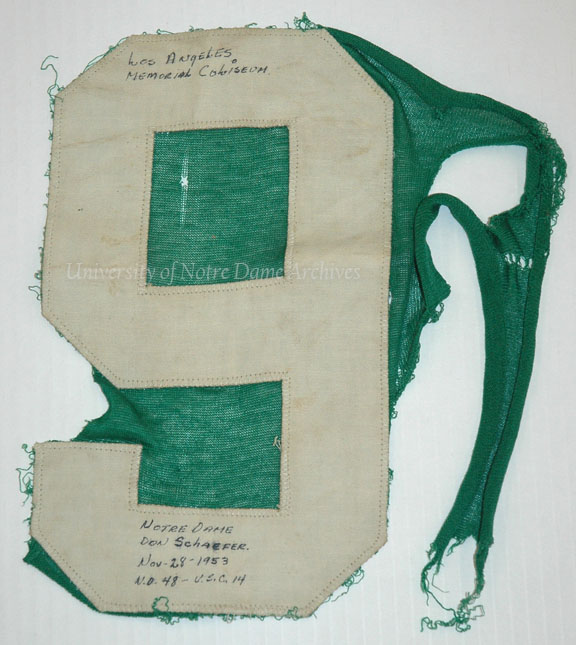 Numeral (#9) worn by player Don Schaefer in the Notre Dame vs. Southern California (USC) football game, 1953/1128.  Felix Quesada Sr. grabbed the jersey as Schaefer was leaving the field.  The tear-away jersey gave way, leaving the number in Quesada's hand.