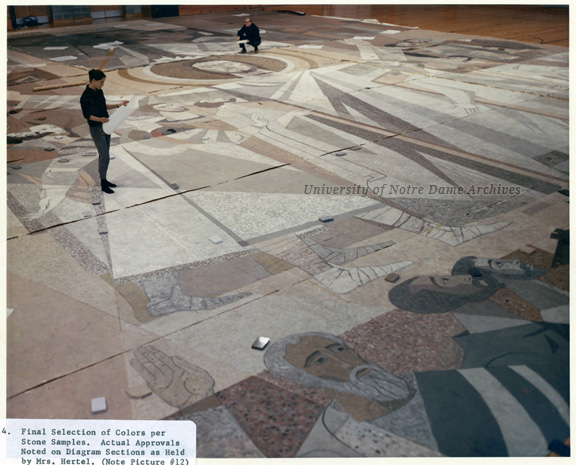Construction of the Word of Life Mural for Memorial Library (later Hesburgh Library), c1962.  Workers, including Mrs. Hertel, are comparing the cast panels to colors per stone samples.