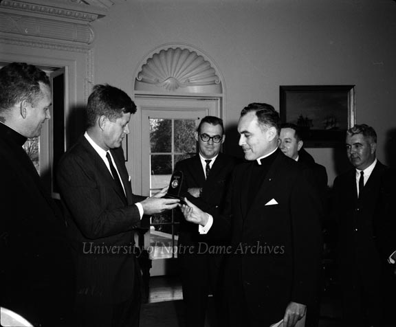 Rev.  Edmund Joyce, CSC, and Rev. Theodore Hesburgh, CSC, presenting President John F. Kennedy with the Laetare Medal in the White House, 1961/1122.