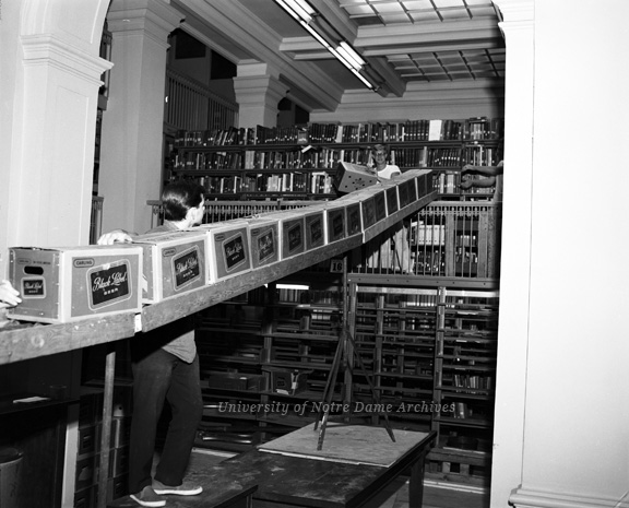 Men (students?) moving books from Lemonnier Library (Bond Hall) to the new Hesburgh Memorial Library in Black Label Beer boxes, c1963.