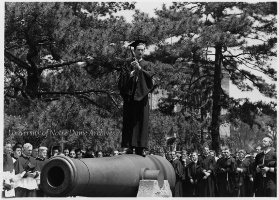 Commencement - Graduating head cheerleader Al Perrine leads the traditional last yell from atop one of the cannons as the class flag is raised on Main Quad while clergy, faculty, and students are gathered around, 1941/0601.