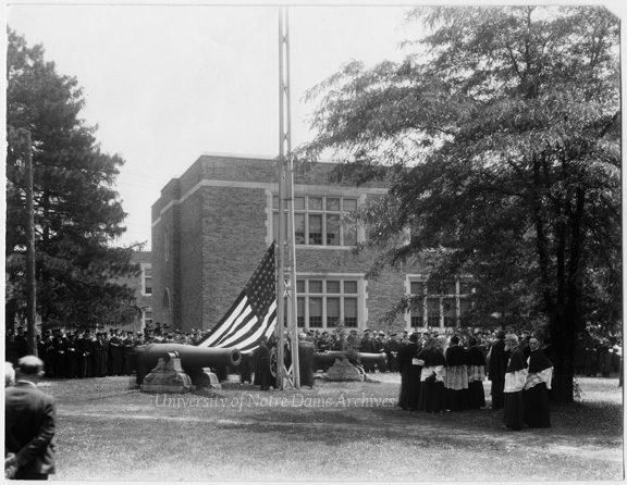 Commencement flag-raising ceremony on Main Quad with the two Civil War cannons, c1930. Hurley Hall is in the background.