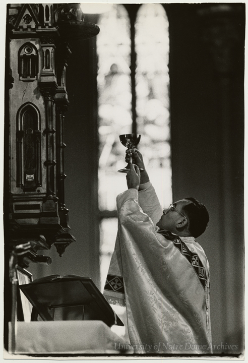 Rev. Theodore M. Hesburgh - priest - holding up a chalice during Mass in the Basilica of the Sacred Heart, 1961. Photo by Paul Fusco, LOOK Magazine [this photo was published in LOOK Magazine, 10/24/1961. The original negatives for this story are at the Library of Congress and may be in the public domain. See LOC rights advisory for more information].