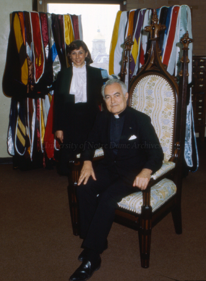 Rev. Theodore M. Hesburgh, CSC, and University Archivist Wendy Clauson Schlereth posing in the University Archives with the academic hoods given to Fr. Hesburgh along with honorary degrees, 1982.