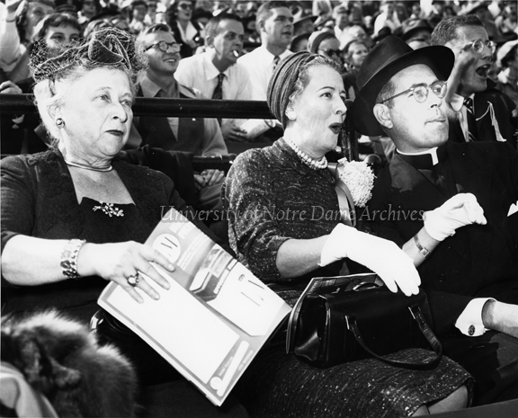 ootball Game Day - Notre Dame vs. Purdue, 1953/1002.  Laetare Medalist Irene Dunne watching the game in the stands with Rev. Theodore M. Hesburgh and Ella Morris.