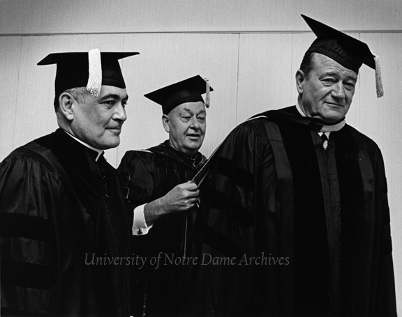 University of Southern California (USC) Commencement - USC President Norman H. Topping adjusting John Wayne's academic robes while Rev. Theodore M. Hesburgh looks on, 1968/0606.
