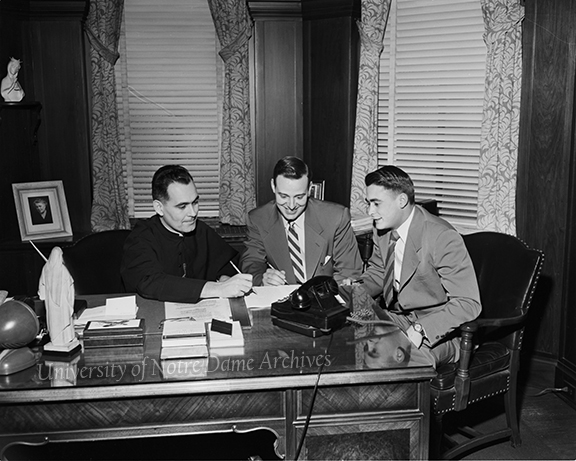 GPHR 45/1739: Rev. Theodore M. Hesburgh planning the first Parents-Son Day (Junior Parents Weekend (JPW)) for April 1953 with Junior Class Officers Jim Richards and Joe Springer, c1952.