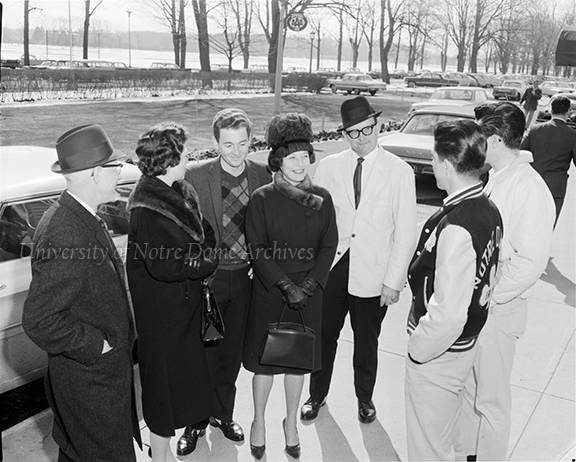 "GPHR 45/4597: Parents-Son Weekend (Junior Parents Weekend (JPW)), March 1963. Caption: ""Mr. and Mrs. Morgan Gibbs of Midland, Mich, (left), chat with Mr. and Mrs. Morris Brenner of Mapletown, Iowa, and their son, Louis, who is an AB Junior and lives off campus. Dick Gibbs is a Science Junior and lives in Morrissey Hall."" Photo by Jack Janowski. This photo was published in ""Notre Dame: A Magazine,"" Summer 1963."