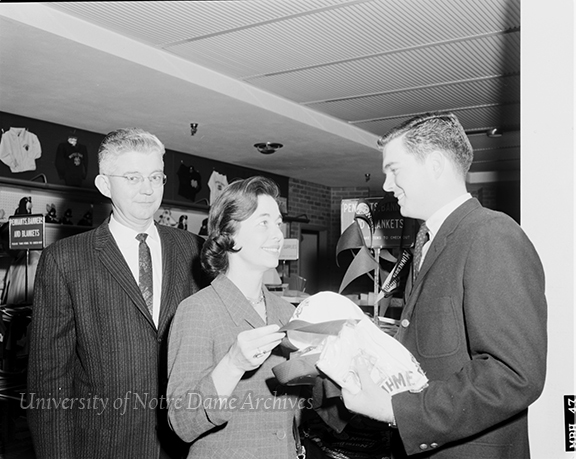 "GPHR 45/4597: Parents-Son Weekend (Junior Parents Weekend (JPW)), March 1963. Caption: ""Mr. & Mrs. W.B. Munson of Denison, Texas, purchase some souvenirs from the Notre Dame Bookstore with their son, Ben, a Junior in Business Administration from Walsh Hall."" Photo by Jack Janowski. This photo was published in ""Notre Dame: A Magazine,"" Summer 1963."