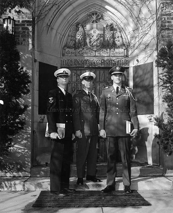GPUB 06/39: Three ROTC students, one member of each military branch (Navy, Air Force, Army), standing in front of the World War I Memorial Door of the Basilica of the Sacred Heart, c1960s-1970s.